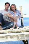 Couple sitting on the pier — Foto de Stock