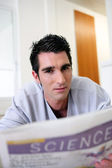 Young man sat reading the newspaper at home — Stock Photo