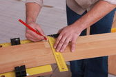 Man measuring slat of parquet — Stock Photo