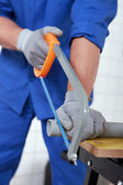 Plumber sawing grey plastic pipe — Stock Photo