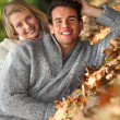 Couple laid in fallen leaves — Stock Photo