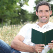 Stock Photo: Smiling mreading book in field