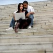 Young couple sitting on steps with a laptop — Stock Photo #18432957