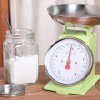 A jar of sugar next to a scale — Stock Photo
