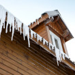 Icicles hanging from a roof edge - Stockfoto