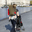 Woman with a pushchair and baby carrier — Stock Photo