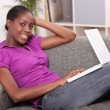 Woman relaxing on sofa with laptop — Stock Photo