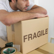 Man leaning on a stack of boxes — Stock Photo