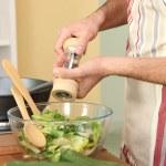 Man seasoning salad — Stock Photo