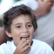 Little boy eating cereal bar outdoors — Stock Photo #18437661