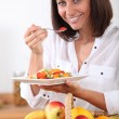 Stock Photo: Womeating fruit salad
