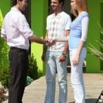 Couple shaking estate-agents hand — Stock Photo
