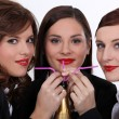 Three businesswomen drinking champagne from straws — Stock Photo