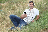 Man listening to music in the park — Stock Photo