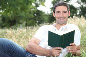 Smiling man reading a book in a field — Stock Photo