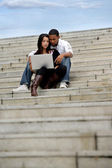 Young couple sitting on steps with a laptop — Stock Photo