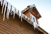 Icicles hanging from a roof edge — Stok fotoğraf