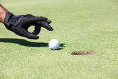 Golfer flicking the ball into the hole with his hand — Zdjęcie stockowe
