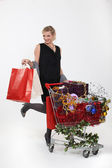 Woman standing by trolley full of Christmas gifts — Stock Photo