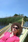 Woman in hammock by lake — Stock Photo