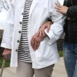 Stockfoto: Assistant helping elderly person walk