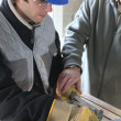 Apprentice learning how to cut sheet metal - Stock Photo