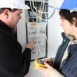 Stock Photo: Two electricians repairing fuse box
