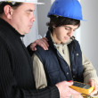 Stock Photo: Electrician and his apprentice with a multimeter