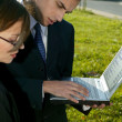 Two business using a laptop outdoors — Stock Photo