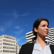 A business woman walking near buildings - Stock Photo