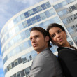 Business couple standing outside an office building — Stock Photo #18445705