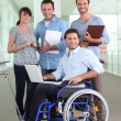 Man in wheelchair working with colleagues - Stockfoto