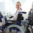 Stock Photo: Womin wheelchair watching presentation