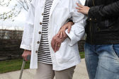 Assistant helping an elderly person walk — Stock Photo