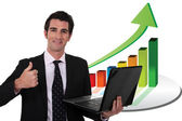 Businessman with a laptop and upward growth chart — Stock Photo