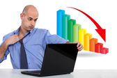Businessman with a downward chart — Stock Photo