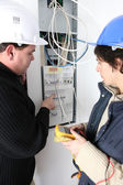 Two electricians repairing fuse box — Stock Photo