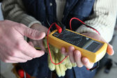 Apprentice using multimeter — Stock Photo