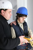 Electrician and his apprentice with a multimeter — Stock Photo