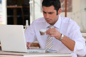 Man using a laptop computer in a cafe — Stock Photo