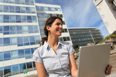 Brunette sat in the city with laptop — Stock Photo
