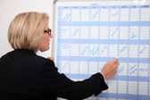 Woman writing on a wall planner — Stock Photo