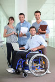 Man in wheelchair working with colleagues — Stock Photo