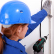 Woman drilling into wall - Stock Photo