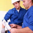 Electrician consulting diagram - Stock Photo