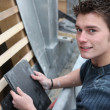 Young man with bitumen roof tiles — Stok fotoğraf