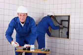 Laborers working on piping — Stock Photo