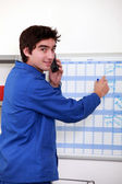 Young worker noting on a slate — Stock Photo