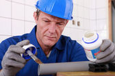 Plumber carefully gluing plastic pipe — Stock Photo
