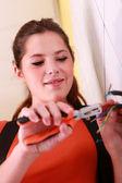 Young woman repairing wiring — Stock Photo